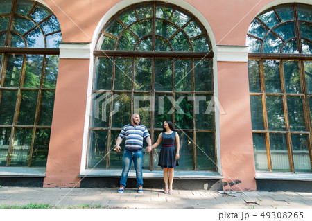 Two people in love stand hugging by large windows 49308265