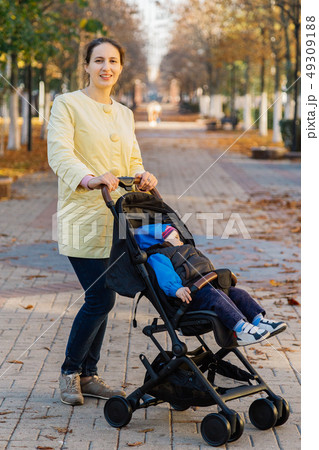 A woman with a child in a stroller walks through 49309188