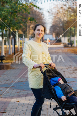 A woman with a child in a stroller walks through 49309190