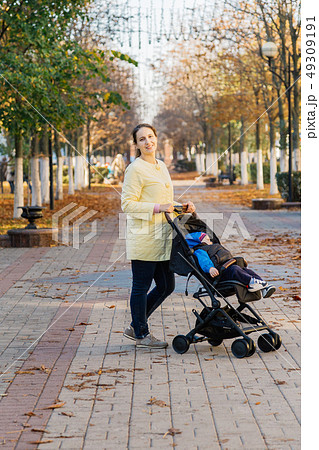 A woman with a child in a stroller walks through 49309191
