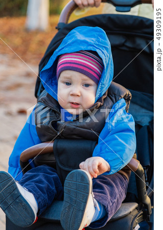 The little baby is sitting in the pram. 49309195