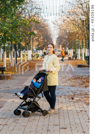 A woman with a child in a stroller walks through 49309196