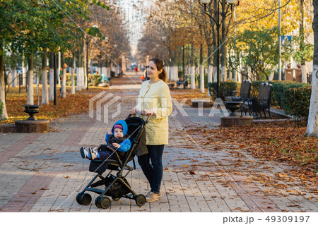 A woman with a child in a stroller walks through 49309197