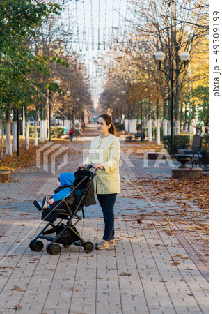 A woman with a child in a stroller walks through 49309199