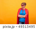 Woman dressed like superhores standing proudly and looking away over yellow background 49313495