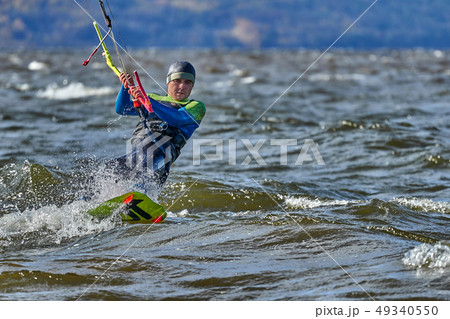 A male kiter slides on the surface of the water. 49340550