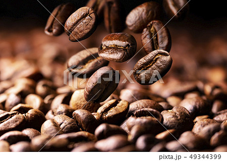 Coffee beans falling on pile, dark background with copy space, close up 49344399