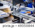 Carpenter worker operating wood cutting machine. 49350844