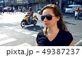 Portrait of a young woman in the city against the background of the road. 49387237