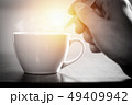 One using spoon mixing hot coffee in the morning 49409942