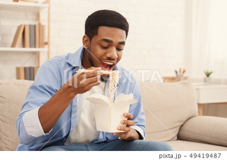 Young black man eating noodles at home 49419487