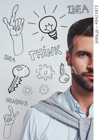 Full of ideas. Vertical half face portrait of a confident bearded man in blue shirt looking at 49423872