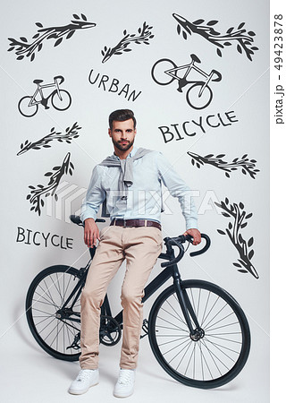 Avoiding traffic. Full length of good looking man with beard leaning on his bicycle against grey 49423878