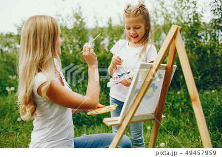 Mother with daughter drawing in a park 49457959
