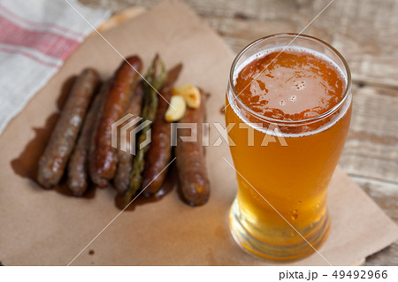Fried sausages and mug of cold beer. 49492966