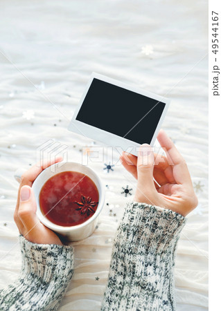 Woman holds a cup of tea and photo. Winter  49544167