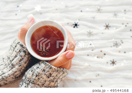Woman holds a cup of hot tea with anise star. 49544168