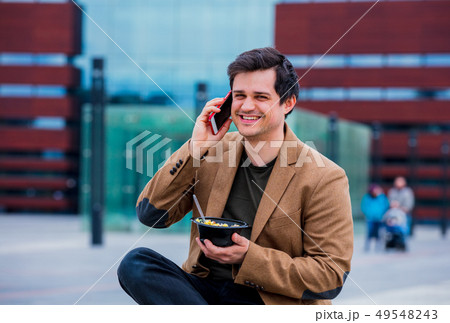 Young businessman with salad and mobile phone at urban city outdoor. 49548243