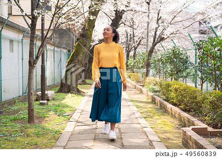 桜並木を歩く黒人女性 49560839