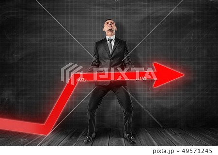 Front view of businessman standing and trying to lift up red graph arrow near black graph ruled wall 49571245