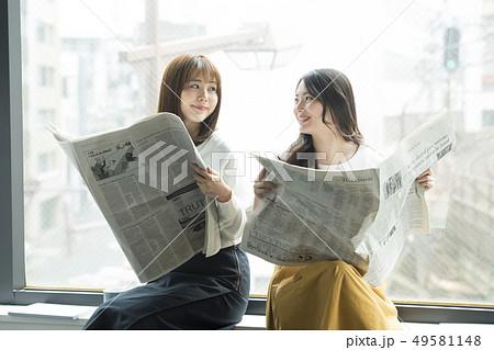 窓辺で新聞を読む女性二人 49581148