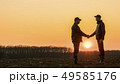 Two farmers on the field shake hands at sunset 49585176