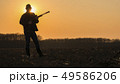 A man with a gun standing in a field at sunset. Opening of the hunting season 49586206