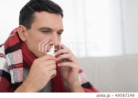 Man with Cold Sitting on Sofa in Checkered Blanket 49587249