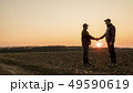 Two farmers on the field shake hands at sunset. Wide lens shot 49590619