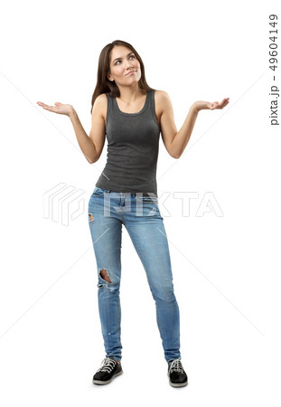 Young woman in gray top and blue jeans standing and shrugging her shoulders with arms bent and 49604149