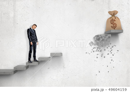 Sad businessman looking down on gray concrete staircase with big money bag at the top of it but with 49604159