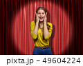 Happy young woman standing and looking at camera with hands on face, in spotlight, against red stage 49604224