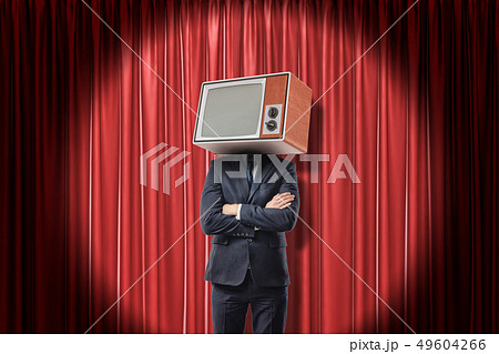Man in suit standing with arms folded, with TV set instead head, in spotlight near red stage curtain 49604266