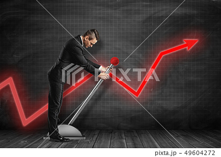 Side view of businessman looking down and pulling big lever near black graph ruled wall with red 49604272