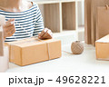 unrecognized seller person packing. box package in a store 49628221