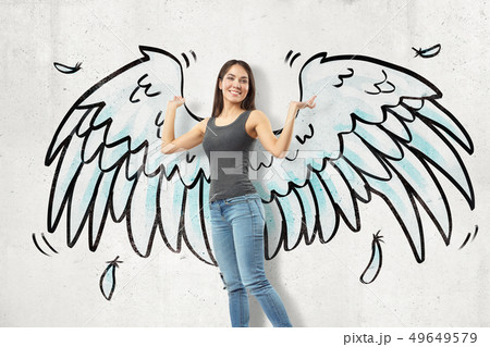 Young brunette girl wearing casual jeans and t-shirt with cartoon wings drawn on white wall 49649579
