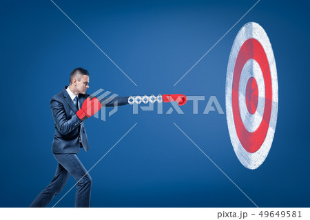 Side view of businessman wearing red boxing gloves and holding out one hand towards big round target 49649581