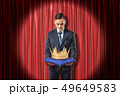 Front view of businessman standing in spotlight against red stage curtain looking down at gold crown 49649583