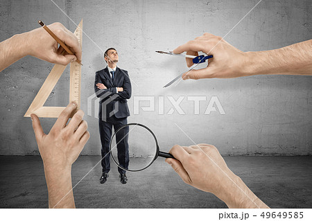 Businessman, arms folded, standing and looking up, and four big hands around measuring him with 49649585
