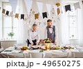 A portrait of a senior and mature man standing indoors in a room set for a party. 49650275