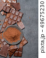 Frame or border made of Dark or milk organic chocolate pieces and cocoa powder on dark concrete 49675230
