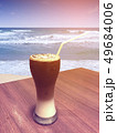 Iced coffee and cream in tall glass with straw on 49684006