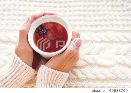 Women holds a cup of hot tea with anise star. 49688709
