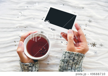 Woman holds a cup of tea and photo. Winter fabric 49688710