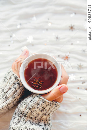 Woman holds a cup of hot tea with anise star. 49688711