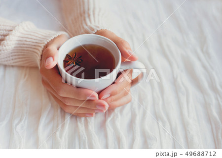 Women holds a cup of hot tea with anise star. Cozy 49688712
