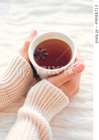Women holds a cup of hot tea with anise star. Cozy 49688713