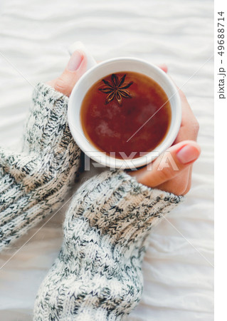 Women holds a cup of hot tea with anise star. Cozy 49688714