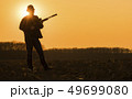 Silhouette of a hunter with a gun. Standing in a field at sunset in full growth 49699080