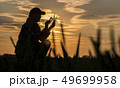 Portrait of a woman agronomist studying wheat shoots through a magnifying glass 49699958